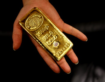 A worker shows a gold bar ready for sale